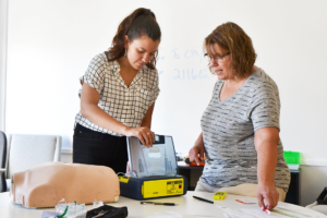 Christy, an associate engineer, learns how to activate the AED's voice prompts during training